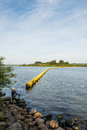 Barrier of floating switched yellow objects wide creek in a dutch nature reserve closed with a plastic Royalty Free Stock Photo