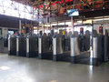 Barriers at a railway or railroad station line of passengers place tickets in the for the doors to open this is Stock Photography