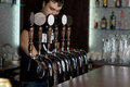 Bartender dispensing draught beer young male standing behind a counter in a pub or club Royalty Free Stock Images