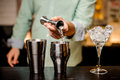 Bartender hands pouring drink into a jigger to prepare a cocktail close up Royalty Free Stock Photo
