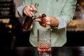 Bartender making alcoholic cocktail , metal jigger and bar environment Royalty Free Stock Photo