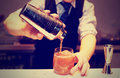 Bartender is making a cocktail toned at bar counter image Royalty Free Stock Photo