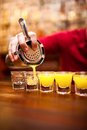 Bartender pouring strong alcoholic drink into small glasses on b Royalty Free Stock Photo