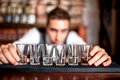 Bartender preparing and lining shot glasses for alcoholic drinks Royalty Free Stock Photo