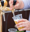 A bartender serving beer at a dispenser in plastic glasses Royalty Free Stock Photo