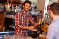 Bartender serving draught beer in bar Royalty Free Stock Photo