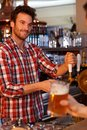 Bartender tapping fresh beer in bar Royalty Free Stock Photos