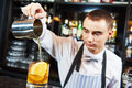 Bartender work at bar young barman worker desk in restaurant preparing coctail Royalty Free Stock Image
