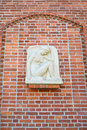 Bas-relief The squating girl & x28;Genius& x29; on a red brick wall. Kaliningrad Royalty Free Stock Photo