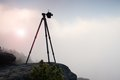 Basalt tripod with professional camera on the peak ready for photography. Sandstone peaks increased from gold foggy background Royalty Free Stock Photo