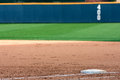 Baseball field shows first base and outfield wall empty highlights Royalty Free Stock Images