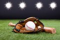 Baseball glove with baseball and bat lying on green grass Stock Photos