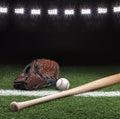 Baseball mitt ball and bat at night under stadium lights Royalty Free Stock Photo