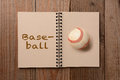 Baseball on open notebook a worn the blank page of a the opposite page has the word spelled out horizontal format a rustic Stock Image