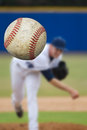 Baseball pitcher a throwing a strike selective focus on the ball coming into close view vertical composition Stock Photos