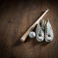 Baseball player equipment on hardwood floor including canvas shoes hardball and bat Royalty Free Stock Image
