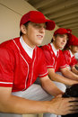 Baseball team mates sitting in dugout player with Royalty Free Stock Photos