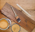 Basic tools for staining wood closeup top view of painting consisting of hand brush stir stick can opener paint lid and full can Royalty Free Stock Image