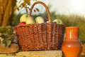 Basket of apple with ceramic pitcher on stone wall in sunshine Royalty Free Stock Photography