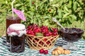 Basket of cherries, cherry jam with biscuit, cherry jam jar and glass of compote Royalty Free Stock Photo