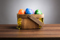 Basket, colored easter eggs on table, gray background Royalty Free Stock Image