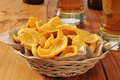 Basket of corn chips and beer a on a bar counter with tall glasses Royalty Free Stock Image