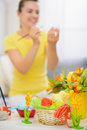 Basket with Easter eggs and painting on egg woman Stock Photos