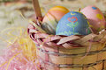 Basket of easter eggs sidelit surrouned by colourful raffia Royalty Free Stock Photo