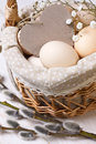 Basket with eggs wooden heart and willow branches on a wooden background Stock Photos
