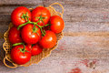 Basket of freshly ripened and cleaned tomatoes overhead view a wicker homegrown in a bunch on the vine displayed on an old Stock Image