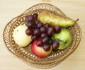 Basket fruits in braided on table Royalty Free Stock Images