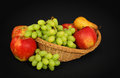 Basket with fruits on dark background Stock Photos