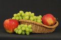 Basket with fruits on dark table Royalty Free Stock Photos