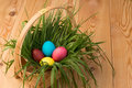 Basket with green grass and Easter eggs on wooden