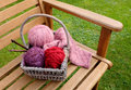 Basket of knitting and yarns on a bench craft patterned balls wool wooden needles garden Stock Photo