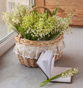 Basket with lilies of the valley convallaria majalis and noteb next to notebook blank pages on o window Royalty Free Stock Photos