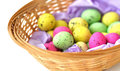 A basket made out of straws and containing vibrant colored eggs for easter Royalty Free Stock Images