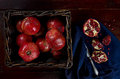 Basket of red pomegranates on a wooden table with silverware Royalty Free Stock Images