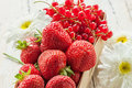 Basket with ripe strawberries and red currants decorated with large daisies. Royalty Free Stock Photo