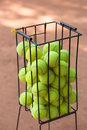 Basket with tennis balls on a court Royalty Free Stock Photography