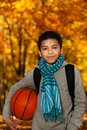 Basketball in autumn handsome black boy years old standing the park under maple trees with orange ball wearing casual clothes with Stock Image