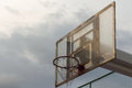 The basketball backboard against stormy sky background and a little sunny ray to hoop dark theme Stock Image