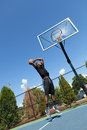 Basketball dunk from below young player driving to the hoop for a high flying slam shallow depth of field Royalty Free Stock Photos