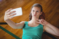 Basketball gesturing while player taking selfie Royalty Free Stock Photo