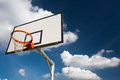 Basketball hoop against lovely blue summer sky with some fluffy white clouds Royalty Free Stock Image