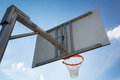 Basketball hoop against lovely blue summer sky with some fluffy white clouds Stock Photo