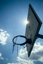 Basketball hoop in the sun a from below with sky Royalty Free Stock Photo