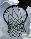A BASKETBALL RIM & NET BELOW THE SILVER CLOUDS - SPORTS - A basket and net hang below a silver lining Royalty Free Stock Photo