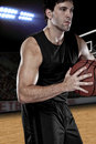 Basketball player with a black uniform on a court Stock Images