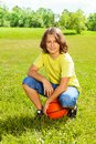 Basketball player after game rest on grass portrait of years old happy smiling boy sit squads with ball the field bright sunny day Royalty Free Stock Photo